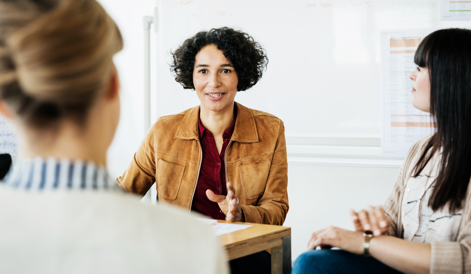Middle aged woman in a conference room setting speaking with two other women.