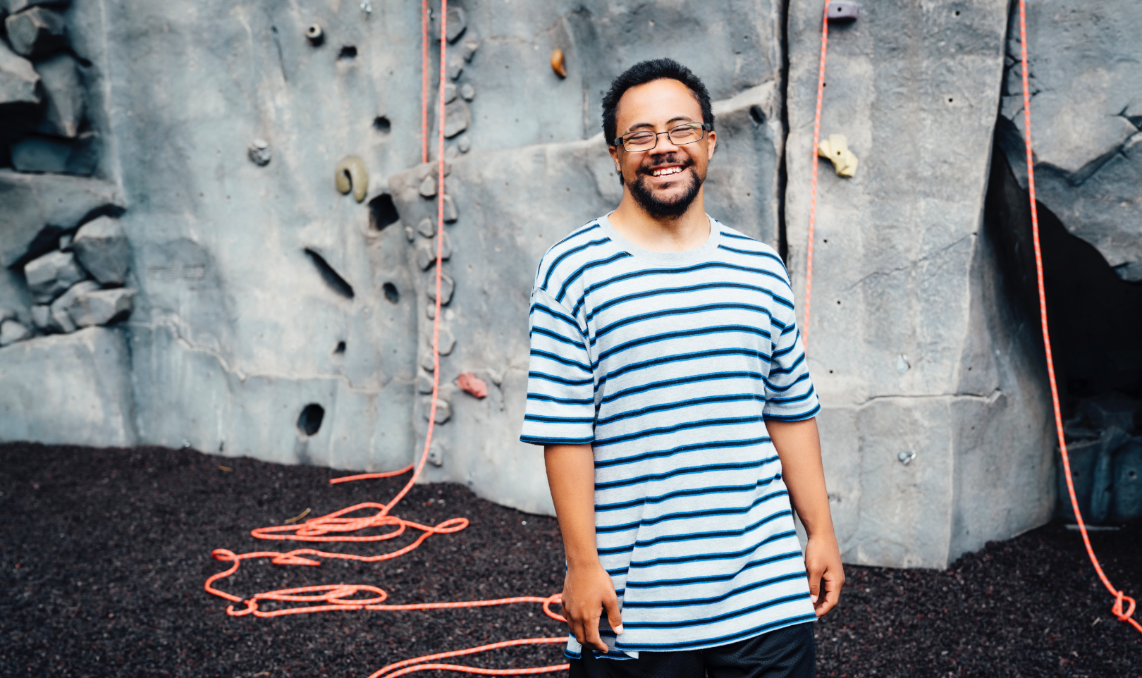 Man standing infront of rock climbing wall smiling